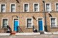 Two blue doors in row housing in suburban london housing in traditional suburbs are usually terrace attached homes like these Royalty Free Stock Photo