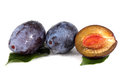 Two blue plums with and half of a plum and leaves Royalty Free Stock Photo