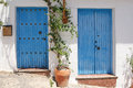 Two blue spanish door in whitewashed wall Royalty Free Stock Photography