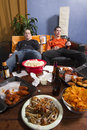 Two bored men watching sports game on tv vertical couch upset and sick from all the junk food while Stock Images