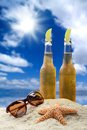 Two bottles of cold beer with lime in a beautiful tropical beach setting blue sunlit sky and clouds sunglasses and starfish Royalty Free Stock Photography