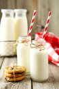 Two bottles of milk with striped straws on the grey wooden background Royalty Free Stock Photo