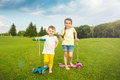 Two boy and a girl standing on the summer green field. Royalty Free Stock Photo
