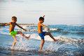 Two boys adolescence playing in the sea water splashing feet wat Royalty Free Stock Photo