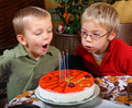 Two boys is blowing candles Royalty Free Stock Images