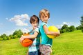 Two boys with boys brothers stand holding balls standing in the park on sunny summer day Stock Photography