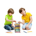 Two boys construct a tower from pencils isolated on white background Stock Images