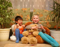 Two boys on the floor with fluffy toys Stock Images