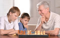 Two boys and grandfather playing chess portrait of at home Royalty Free Stock Photo