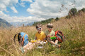 Two boys have got picnic in mountain field Royalty Free Stock Photo