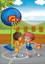 Two boys playing basketball at the basketball court Royalty Free Stock Photo