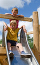 Two boys playing on a slide playground Royalty Free Stock Photo