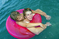 Two boys in a rubber ring have fun in the ocean Stock Photo