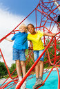 Two boys stand hugging on red ropes of net caucasian and african in a hug playground in summer Stock Photography