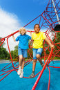 Two boys stand together on red ropes of net Royalty Free Stock Photo