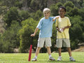 Two boys standing on grass in park with softball bat and ball smiling portrait Stock Photography