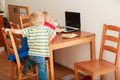 Two boys using laptop computer playing games Royalty Free Stock Photo