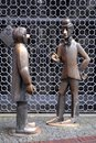 Two bronze sculptures in front of a metal grate in Cologne in Germany Royalty Free Stock Photo