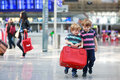 Two brother boys going on vacations trip at airport little sibling having fun and with suitcase indoors Stock Images