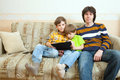Two brothers and father sit on sofa with tablet pc Stock Images