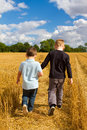 Two brothers holding hands in the wheat fields Royalty Free Stock Photo