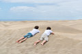 Two brothers lie on the sand dune and looking into the distance Stock Photo