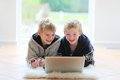 Two brothers lying on the floor with laptop Royalty Free Stock Photo