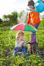 Two brothers play in rain outdoors Royalty Free Stock Photography