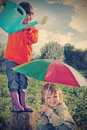 Two brothers play in rain outdoors Stock Photos