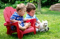 Two brothers and puppy little laugh as they play with a small white Stock Photo