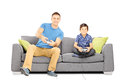 Two brothers seated on a sofa playing video games isolated white background Royalty Free Stock Photos