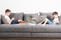 Two brothers sits in the opposite side of the sofa and looks on tablet computers. Royalty Free Stock Photo