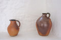 Two brown pottery jugs traditional clay against a stone white wall background Stock Images