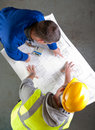 Two builders discuss construction blueprints Royalty Free Stock Photos