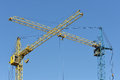 Two building crane yellow and blue visually inters intersect depicted against the clear sky Royalty Free Stock Photos