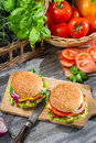 Two burgers fresh vegetables old wooden table Royalty Free Stock Photos