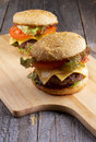 Two burgers tasty hamburgers with beef tomato lettuce pickle red onion and cheese into sesame buns closeup on wooden cutting board Stock Photography