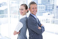 Two business colleagues standing back to back in the office Stock Images