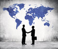 Two business men shaking hands and a blue cartography of the world above Royalty Free Stock Photography