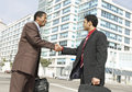 Two business men shaking hands on city street multiethnic against buildings Royalty Free Stock Photography