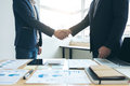 Two business men shaking hands during a meeting to sign agreemen Royalty Free Stock Photo