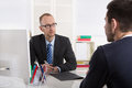 Two business men sitting in the office: meeting or job interview