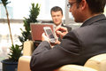 Two business men working with laptop & palmtop in the office environment. Royalty Free Stock Photo
