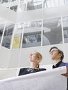 Two business people with blueprint in office low angle view of smiling atrium Stock Images