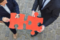 Two business people solving jigsaw big red puzzle pieces together Royalty Free Stock Images