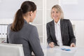 Two business woman sitting at desk: customer and adviser talking Royalty Free Stock Photo