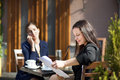 Two business women sitting at a table in a cafe on the street Royalty Free Stock Photography