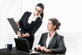 Two business women talking over a contract young one standing up and one sitting at desk with laptop discussing about on clipboard Royalty Free Stock Photo