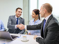 Two businessman shaking hands in office business technology and concept smiling Royalty Free Stock Photo