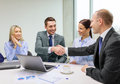 Two businessman shaking hands in office business technology and concept smiling Royalty Free Stock Photography
